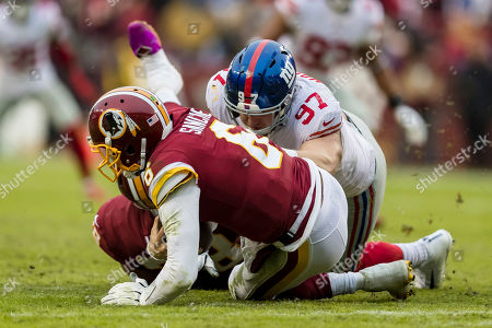 Washington Redskins quarterback Mark Sanchez (6) is sacked by New York Giants defensive end Josh Mauro (97) during the second half of the NFL game between the New York Giants and the Washington Redskins at FedExField in Landover, Maryland