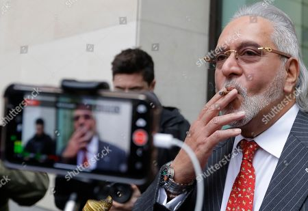 Indian business man Vijay Mallya is filmed by the media as he takes a smoking break outside Westminster Magistrates Court in London, . A British judge is expected to rule on whether wealthy Indian entrepreneur Vijay Mallya will be extradited to India to face fraud allegations