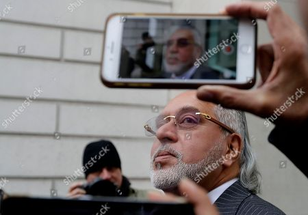Indian business man Vijay Mallya speaks to the media as he takes a smoking break outside Westminster Magistrates Court in London, . A British judge is expected to rule Monday on whether wealthy Indian entrepreneur Vijay Mallya will be extradited to India to face fraud allegations
