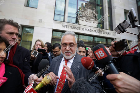 Indian business man Vijay Mallya, centre, is surrounded by the media as he leaves Westminster Magistrates Court in London, . A British court has ordered that charismatic Indian tycoon Vijay Mallya should face extradition to India on financial fraud allegations