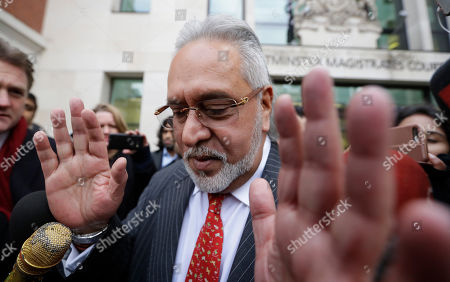 Indian business man Vijay Mallya is surrounded by the media as he leaves Westminster Magistrates Court in London, . A British court has ordered that charismatic Indian tycoon Vijay Mallya should face extradition to India on financial fraud allegations
