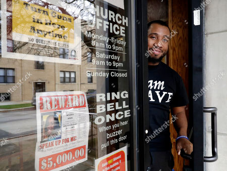 Lamar Johnson stands for a portrait at St. Sabina Church in Chicago, . Johnson, 28, is a counselor for the church program, B.R.A.V.E. Youth Leaders. He teaches kids as young as 6 how to speak out against gun violence and be social justice activists. The church also offers rewards for community members who provide tips that help police solve murders. The window shows a poster seeking help in finding the gunman who fatally shot a 21-year-old woman in the community in July