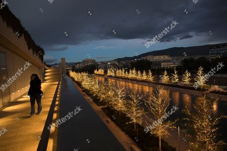 A woman walks in front of trees decorated with Christmas light at the Stavros Niarchos Foundation Cultural Center in Athens, on