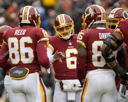 Washington Redskins quarterback Mark Sanchez (6) discusses strategy with tight end Jordan Reed (86) and tight end Vernon Davis (85) in the first quarter of the game against the Washington Redskins at FedEx Field in Landover, Maryland. The Giants won the game 40 - 16.