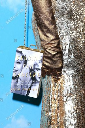 Leslie Zemeckis wears a bag made of the cover of her book titled 'Feuding Fan Dancers' as she