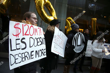 Protesters stand outside the site of the CBS shareholder's meeting in New York, . The meeting in New York wrapped up quickly after 11 board members were elected. The new board has until the end of January to decide whether former CEO Les Moonves, who was ousted in September after multiple allegations of sexual misconduct, will receive his $120 million severance package