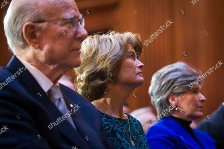 Senate Agriculture Committee Chairman Pat Roberts, of Kanas, left, Sen. Lisa Murkowski, R-Alaska, center, and Sen. Joni Ernst, R-Iowa, watch as acting Environmental Protection Agency administrator Andrew Wheeler signs an order withdrawing federal protections for countless waterways and wetlands at EPA headquarters in Washington