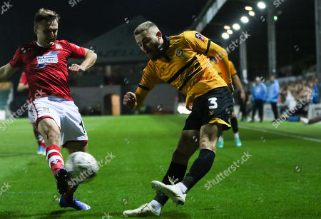 Dan Butler of Newport County crosses as Paul Rutherford of Wrexham challenges