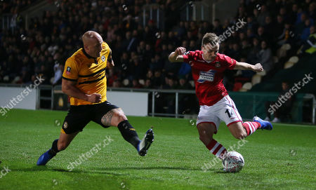 Paul Rutherford of Wrexham has his cross blocked by David Pipe of Newport County.