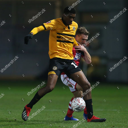 Tyreeq Bakinson of Newport County is challenged by Paul Rutherford of Wrexham.
