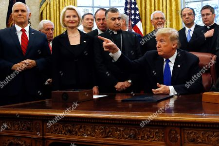 "Donald Trump, Mike Pence, Callista Gingrich. Vice President Mike Pence, far left, next to Callista Gingrich, U.S. Ambassador to the Holy See, listen as President Donald Trump calls on a reporter after signing H.R. 390, the ""Iraq and Syria Genocide Relief and Accountability Act of 2018,"" in the Oval Office of the White House, in Washington"
