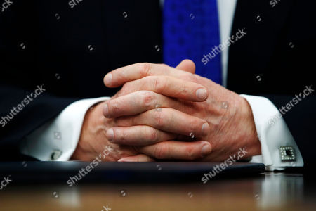 """President Donald Trump's hands are folded as he speaks about H.R. 390, the """"Iraq and Syria Genocide Relief and Accountability Act of 2018,"""" in the Oval Office of the White House, in Washington"""