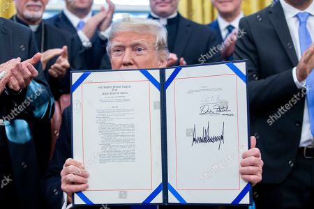 US President Donald J. Trump (C) holds up H.R. 390, the 'Iraq and Syria Genocide Relief and Accountability Act of 2018', after signing it beside lawmakers and religious leaders in the Oval Office of the White House in Washington, DC, USA, 11 December 2018. The law will provide emergency humanitarian and recovery assistance to victims of crimes against humanity, war crimes and genocide in Iraq and Syria. The legislation also directs the US State Department to preserve evidence of genocide in those regions.