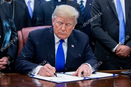 US President Donald J. Trump signs H.R. 390, the 'Iraq and Syria Genocide Relief and Accountability Act of 2018', in the Oval Office of the White House in Washington, DC, USA, 11 December 2018. The law will provide emergency humanitarian and recovery assistance to victims of crimes against humanity, war crimes and genocide in Iraq and Syria. The legislation also directs the US State Department to preserve evidence of genocide in those regions.