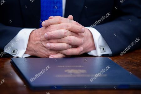 The hands of US President Donald J. Trump during a signing ceremony for H.R. 390, the 'Iraq and Syria Genocide Relief and Accountability Act of 2018', in the Oval Office of the White House in Washington, DC, USA, 11 December 2018. The law will provide emergency humanitarian and recovery assistance to victims of crimes against humanity, war crimes and genocide in Iraq and Syria. The legislation also directs the US State Department to preserve evidence of genocide in those regions.