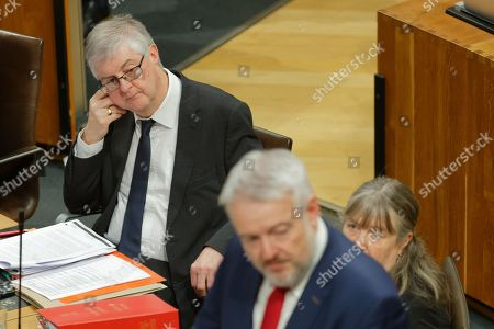 Successor Mark Drakeford (L) looks on as First Minister for Wales Carwyn Jones (R) speaks
