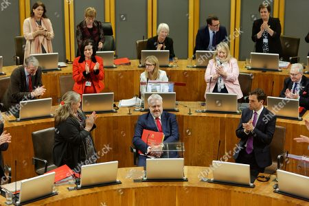First Minister for Wales Carwyn Jones (C) is applauded by colleagues