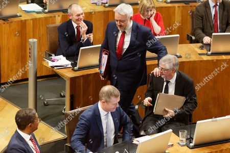 Stock Image of First Minister for Wales Carwyn Jones (C) touches his successor Mark Drakeford as he walks out of the Senedd
