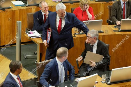 First Minister for Wales Carwyn Jones (C) touches his successor Mark Drakeford as he walks out of the Senedd