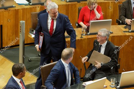 Stock Photo of First Minister for Wales Carwyn Jones (C) touches his successor Mark Drakeford as he walks out of the Senedd