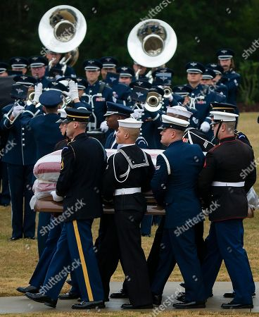 The flag-draped casket of President George H.W. Bush is carried past a military band to a burial plot close to his presidential library for internment, in College Station, Texas