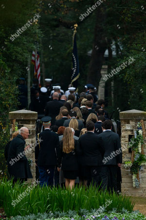 Stock Picture of Friends and family, including former Secretary of State James Baker, bottom left, follow the flag-draped casket of President George H.W. Bush as he is carried to the burial plot close to his presidential library for internment, in College Station, Texas