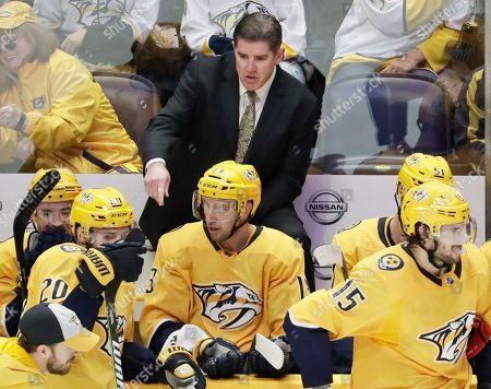 Nashville Predators head coach Peter Laviolette talks with his players in the third period of an NHL hockey game against the Ottawa Senators, in Nashville, Tenn. The Predators won 3-1
