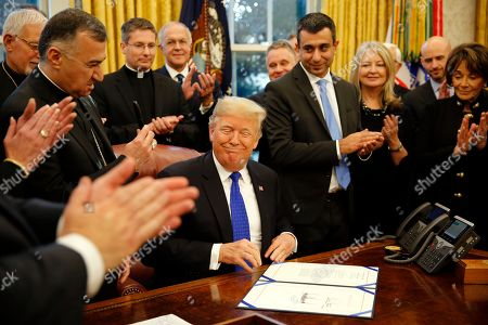 """United States President Donald J. Trump signs H.R. 390, the """"Iraq and Syria Genocide Relief and Accountability Act of 2018"""" in the Oval Office of the White House, in Washington, DC."""