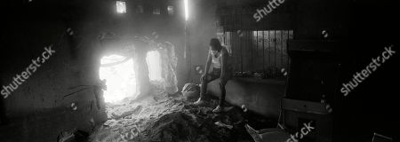 An exhausted Angelica Maria Alvarez takes a breather inside her home that was destroyed by Volcano of Fire eruption, in San Miguel Los Lotes, Guatemala. Ten days after the volcano blew, Alvarez continued looking for her husband, two daughters, and more than nine relatives in a house turned to twisted iron and hot ashes