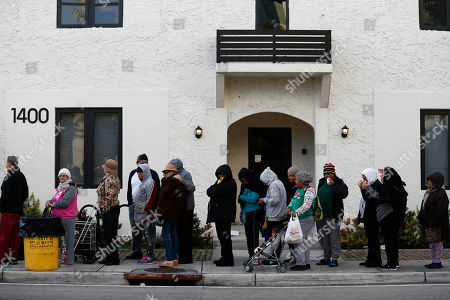 People stand outside in a line waiting for a food drive charity event to begin, in the Little Havana neighborhood of Miami