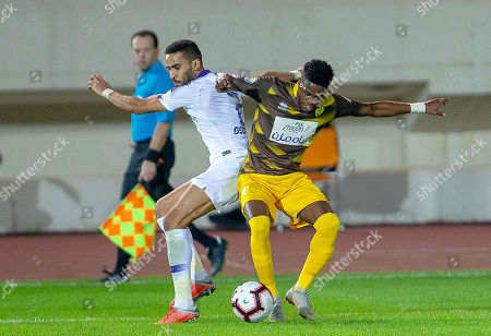 Stock Photo of Al-Hilal's Mohammed Al-Breik (L) in action against Ohod's Adolphe Teikeu (R) during the Saudi Professional League soccer match between Ohod Club and Al-Hilal S. FC in Medina, Saudi Arabia, 12 December 2018.