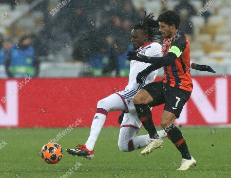 Lyon's Bertrand Traore, left, challenges for the ball with Shakhtar Taison during the Group F Champions League soccer match between Shakhtar Donetsk and Lyon at the Olympiyskiy stadium, in Kiev, Ukraine, Wednesday, Dec.12, 2018
