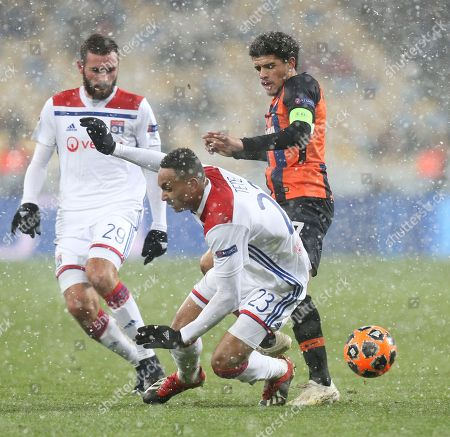 Lyon's Kenny Tete, centre, challenges for the ball with Shakhtar Taison during the Group F Champions League soccer match between Shakhtar Donetsk and Lyon at the Olympiyskiy stadium, in Kiev, Ukraine, Wednesday, Dec.12, 2018