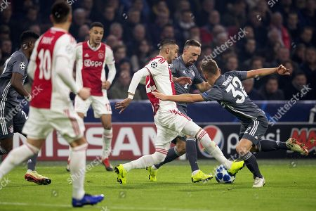 Stock Photo of Hakim Ziyech of Ajax in duel with Joshua Kimmich and Frank Ribery of Bayern  during the UEFA Champions League Group E soccer match between Ajax Amsterdam and FC Bayern Muenchen in Amsterdam, Netherlands, 12 December 2018.