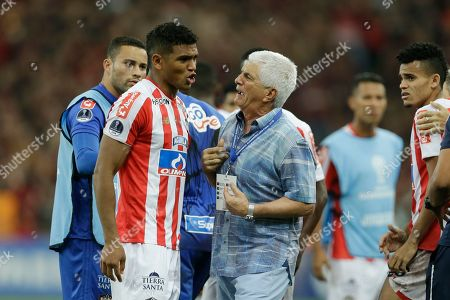 Julio Comesana, coach of Colombia's Junior, talks to Rafael Perez after losing the Copa Sudamericana final soccer match against Brazil's Atletico Paranaense at the Arena da Baixada stadium in Curitiba, Brazil, . Atletico Paranaense beat Colombia's Junior 4-3 on penalties after the match ended 1-1 after extra time