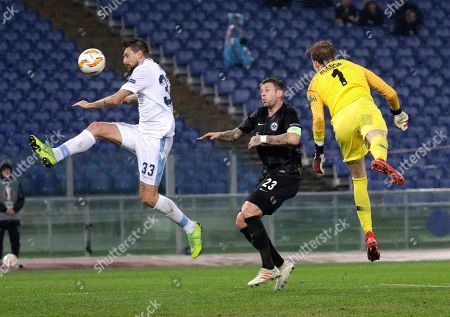 Lazio's Francesco Acerbi, left, trie to score past Frankfurt's Marco Russ, center, and Frankfurt goalkeeper Frederik Ronnow during a Europa League, Group H soccer match between Lazio and Eintracht Frankfurt at Rome's Olympic stadium, Thursday, Dec.13, 2018
