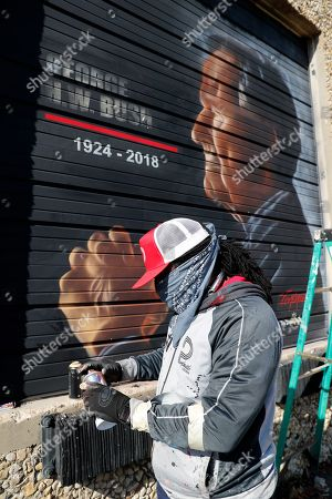 Artist Theo Ponchaveli works on painting a mural of the late president, George H. W, Bush, in Richardson, Texas. Ponchaveli painted the mural on the exterior door of The Drawing Board, the office building where his gallery is located