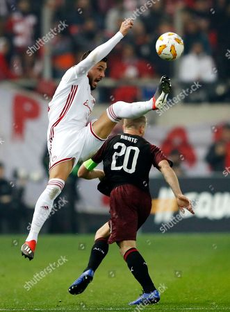 Olympiakos' Miguel Ángel Guerrero, left, challenges for the ball with AC Milan's Ignazio Abate during a Group F Europa League soccer match between Olympiakos and AC Milan at Georgios Karaiskakis stadium in the port of Piraeus, near Athens