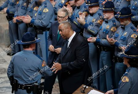 John Batiste, Jay Inslee. Washington State Patrol Chief John Batiste, center, greets a new trooper during a graduation ceremony, as Gov. Jay Inslee looks on in the Rotunda at the Capitol, in Olympia, Wash. The class of 31 troopers completed more than 1,000 hours of training and will now work for the WSP across the state
