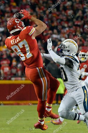 Stock Photo of Kansas City Chiefs tight end Travis Kelce (87) makes a catch against Los Angeles Chargers defensive back Desmond King (20) during the first half of an NFL football game in Kansas City, Mo