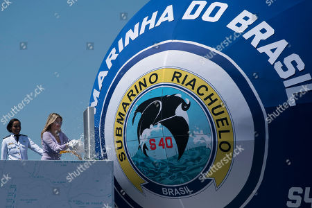 Brazil's first lady Marcela Temer smashes a bottle of sparkling wine on the new submarine Riachuelo during a ceremonial launch party at the Itaguai Naval Complex in Itaguai, Brazil, . This is the first of five submarines built with French technology