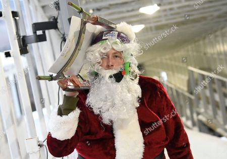 Former 2014 Luge Olympian Aidan Kelly, of West Islip, N.Y., dresses as Santa Claus for a training run on the Luge World Cup track, in Lake Placid, N.Y