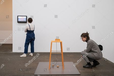 A woman looks at the artwork 'Kartoffelmaschine -Apparat, mit dem eine Kartoffel eine andrere umkreisen kann' (lit. Potato machine -deveice with which one potato can circle another) by US sculptor George Segal during the exhibition 'Local Histories' at the Hamburger Bahnhof Museum in Berlin, Germany, 14 December 2018. The exhibition of artworks from the Friedrich Christian Flick Collection will be open to public until 29 September 2019.