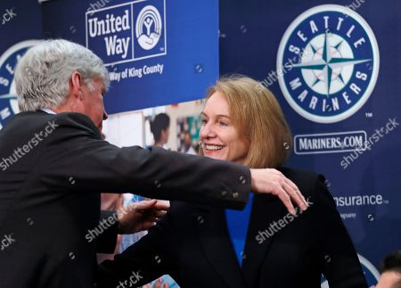 Seattle Mariners chairman John Stanton, left, embraces Mayor Jenny Durkan during a news conference announcing the launch of a community partnership, Home Base, to help tackle King County's homelessness crisis, in Seattle. The Mariners have pledged $3 million for a new effort to prevent low-income renters facing eviction from falling into homelessness. The team's contribution to the Home Base partnership will beef up staffing at the Housing Justice Project, a legal clinic sponsored by the King County Bar Association that provides legal advice and counsel to area renters. The partnership will also provide funding to help tenants facing eviction pay fines and back rent. The partners estimate they could help as many as 4,000 people