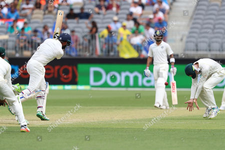 India's Cheteshwar Pujara hits the ball as Australia's Peter Handscomb ducks during play in the second cricket test between Australia and India in Perth, Australia