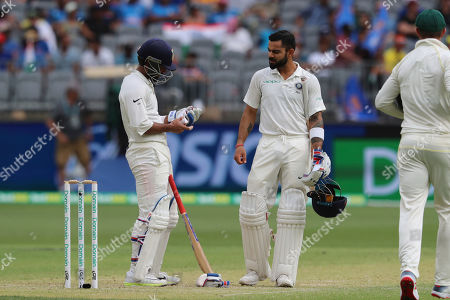 India's Ajinkya Rahane, left, holds his hand after being hit as Virat Kohli looks on during play in the second cricket test between Australia and India in Perth, Australia