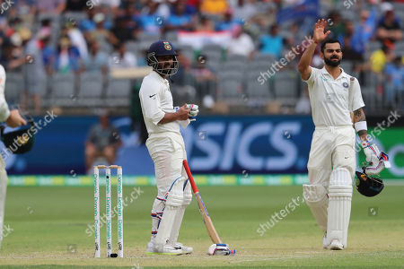 India's Ajinkya Rahane, left, holds his hand after being hit as Virat Kohli calls for medical assistance during play in the second cricket test between Australia and India in Perth, Australia