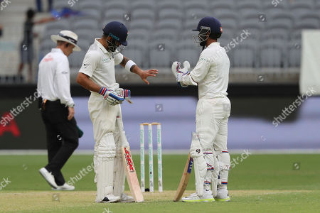 Virat Kohli, Ajinkya Rahane. India's Virat Kohli, left, checks his hand that he appeared to injure in a run out attempt as Ajinkya Rahane looks, during play in the second cricket test between Australia and India in Perth, Australia