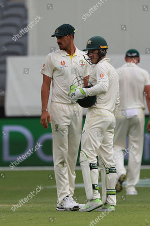 Stock Photo of Australia's skipper Tim Paine, right, confers with bowler Mitchell Starc during play in the second cricket test between Australia and India in Perth, Australia