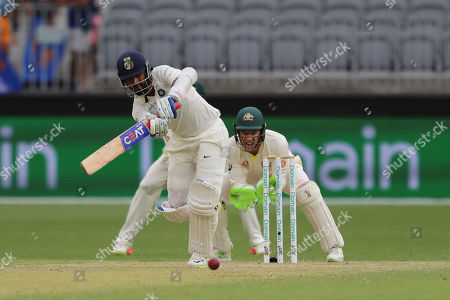 Stock Picture of Ajinkya Rahane, Tim Paine. India's Ajinkya Rahane bats in front of Australia's Tim Paine during play in the second cricket test between Australia and India in Perth, Australia
